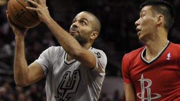 San Antonio Spurs guard Tony Parker, left, of France, shoots sd Houston Rockets guard Jeremy Lin watches during the first half of an NBA basketball game on Wednesday, Dec. 25, 2013, in San Antonio. (AP Photo/Darren Abate)